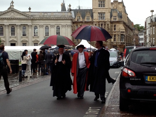 Dons walking in the rain at Cambridge graduation.