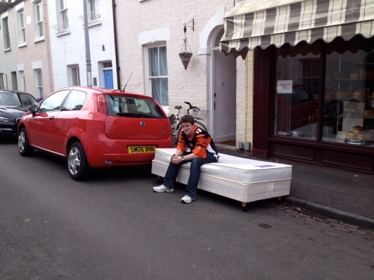 Why is this man sitting on a bed in the street?